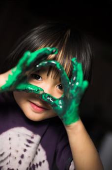 child looking through paint covered hands