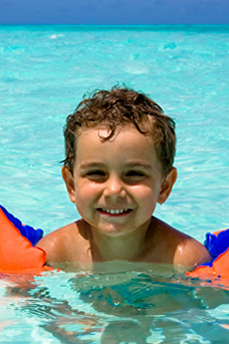child swimming with floaties